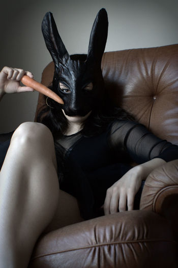 Portrait of sensuous woman in rabbit mask sitting on couch at home