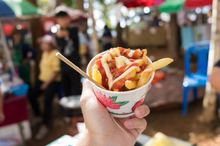 Close-up of hand holding french fries in bowl