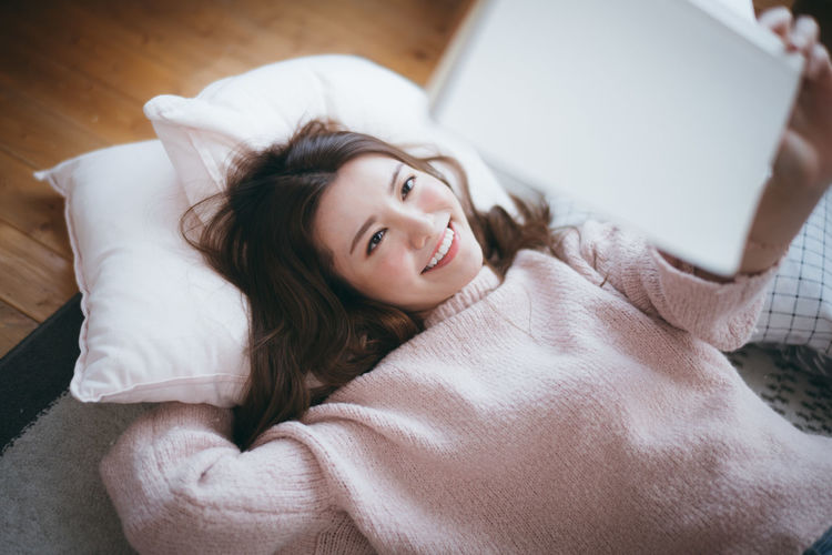 Portrait of smiling young woman lying on bed at home