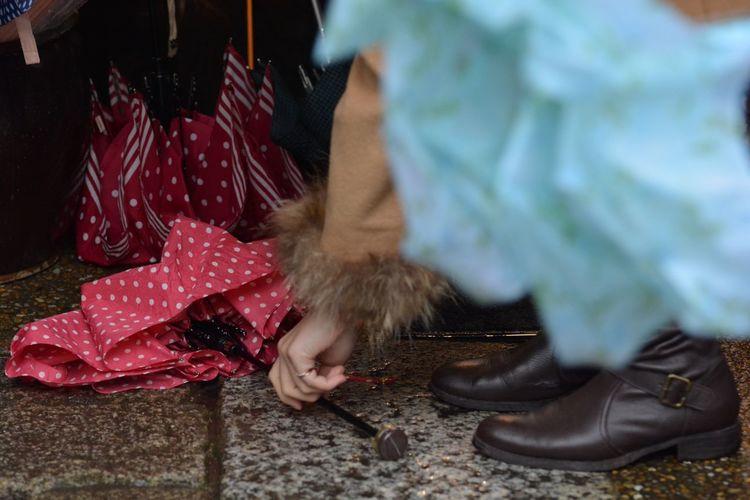 Woman Picking Up Umbrella