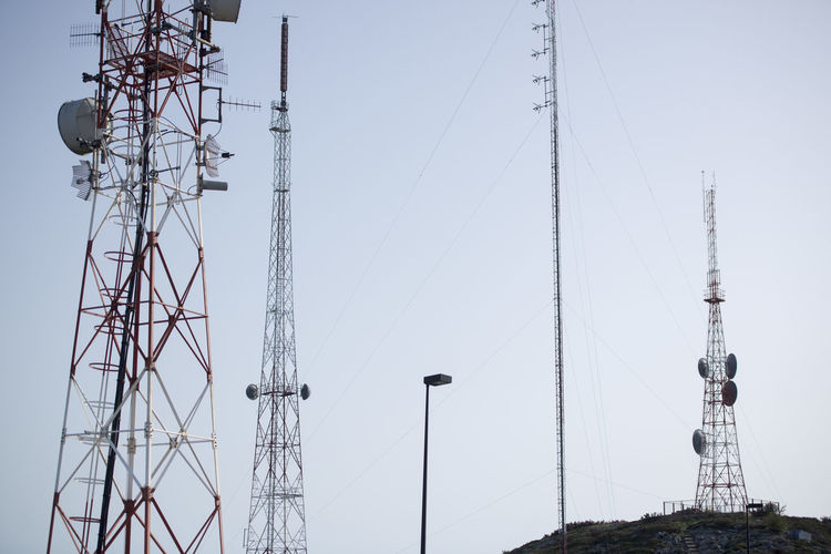 Low angle view of communications tower against clear sky during sunny day