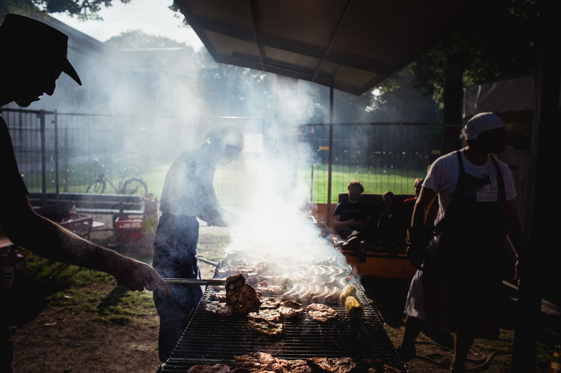People grilling meat at barbeque grill
