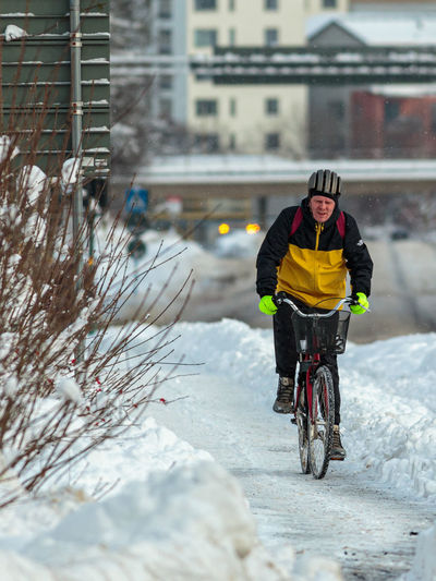 Full length of man riding bicycle on snow in city