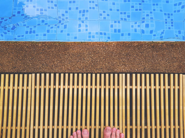 Low section of person standing at poolside