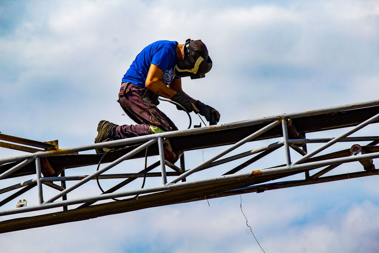 Low angle view of man working on metallic structure against sky