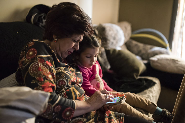 Grandmother playing with granddaughter at phone 60 Years Old Bonding Care Cat Child Childhood Communication Domestic Life Family Family Females Girls Granddaughter Grandma Grandmother Grandson Indoors  Lifestyles Living Room Mother Phone Play Sofa Togetherness Two People
