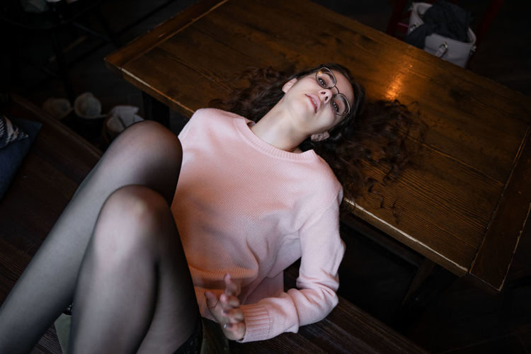 Portrait of woman lying on table at home