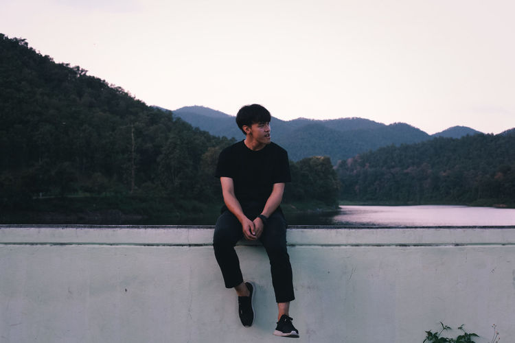 Full length of young man sitting on retaining wall against river and forest
