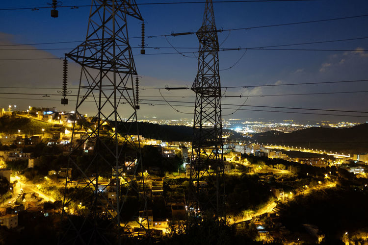 Low angle view of electricity pylon at night