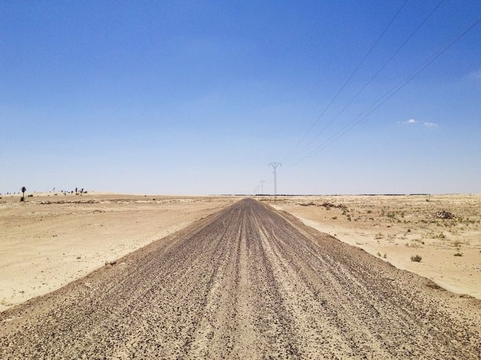 Road amidst desert land against clear blue sky