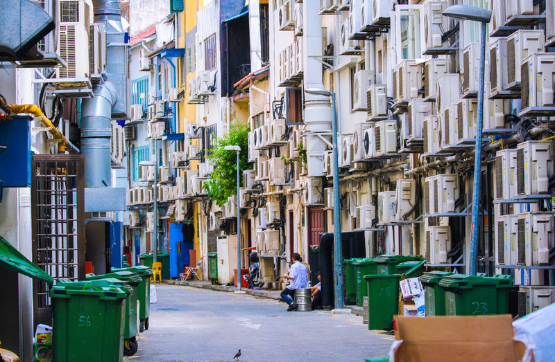 Man Sitting On Container Amidst Buildings