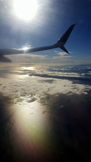 Plane View From Above Plane Window Plane Window View Sunshine Sky Sky And Clouds Relaxing Looking Through No People Up Above The World So High Flying Travel Travelling Plane Wing Water Ocean Let's Go. Together. Perspectives On Nature