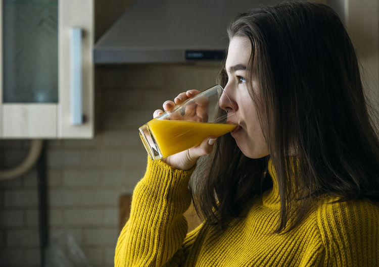 Teen girl drinks orange juice at home by the window