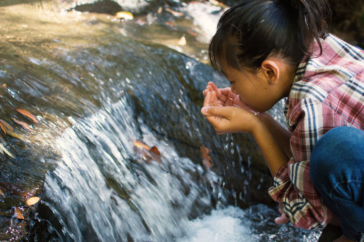 Girl drinking water from waterfall