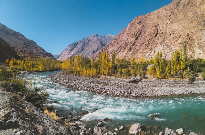 Gilgit river flowing through Gupis, with a view of mountain range and trees in autumn. Ghizer, Gilgit Baltistan, Pakistan. River Flowing Water Gilgit Baltistan Winding River River Current Blue Sky Blue Water Turquoise Colored Green Valley Gupis Ghizer Autumn Travel Destinations Eco Tourism Environment Ecology Freshness Fresh Water Clean Air Nature Landscape Panorama View Panoramic View Scenery Scenics Climate Forest Mountain Range Mountains Stream Countryside Watercourse Wilderness Area Trekking Hiking Adventure Leisure Vacations Peaceful Peace And Quiet Serenity Tranquility Clear Sky Pure Nature Pollution Free Fall Journey Pebbles And Stones Backpacking Tranquil Scene Beauty In Nature Non-urban Scene No People Day Rock Idyllic Plant Remote Outdoors
