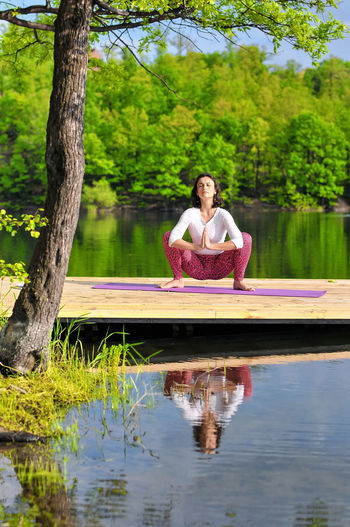 Yoga practicing over the beautiful lake. Beauty In Nature Exercise Time Eyes Closed  Floating Platform Forest In Background Healthy Lifestyle Lake Lake Yoga Namaskarasana Nature Reflection Relaxation Relaxation Exercise Salutation Pose Tranquil Scene Tranquility Wellbeing Wooden Platform Yoga Yoga Exercise Yoga Mat Yoga Over Lake Yoga Pose