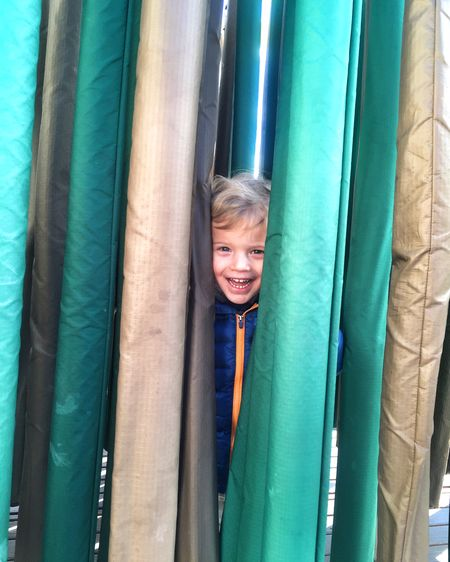 Portrait of happy boy peeking through fabrics