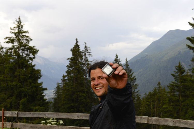 Portrait of smiling man holding digital stopwatch while standing by railing on mountain against sky