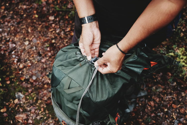 MAN HIKERS TYING / TIE HIS BACKPACK AT NATURE OUTDOOR/PARK. VIEW OF LEG AND HAND. OUTDOOR SPORT & TIE CONCEPT. Backpacking Extreme Rock Tying Adventure Autumn Backpack Change Day Field Hand High Angle View Hiker Holding Human Body Part Human Hand Land Leaf Leaves Leisure Activity Lifestyles Men Midsection Mountain Nature One Person Outdoors Plant Part Real People Sort Tie