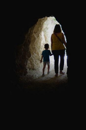 Mother and son walking out of a carved tunnel Light Woman Child Dark Leisure Activity Lifestyles Light At The End Of The Tunnel Nature People Rear View Rock Rock - Object Tunnel Two People Walking