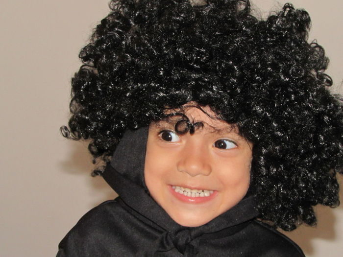 Close-Up Of Cheerful Boy Wearing Wig At Home