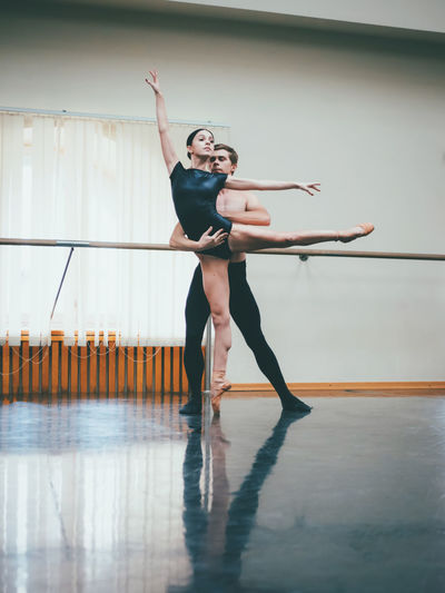 Full Length Of Dancers Dancing In Ballet Studio