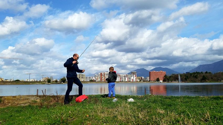 Green Color Colorful people and places People Fishing On The Lake Artificial Lake Of Tirana Cityscape Clouds And Sky Reflections In The Water Tree Family Time Daddy Son Time This Is Family