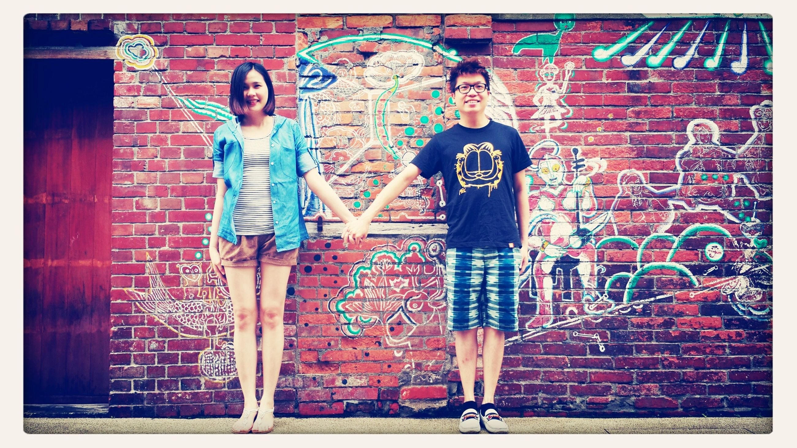 transfer print, auto post production filter, lifestyles, full length, standing, young adult, leisure activity, front view, casual clothing, person, wall - building feature, graffiti, young women, looking at camera, portrait, three quarter length, built structure