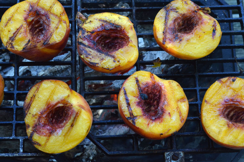 Peach halves grilling on top of a small tabletop hibachi grill on picnic table outdoors