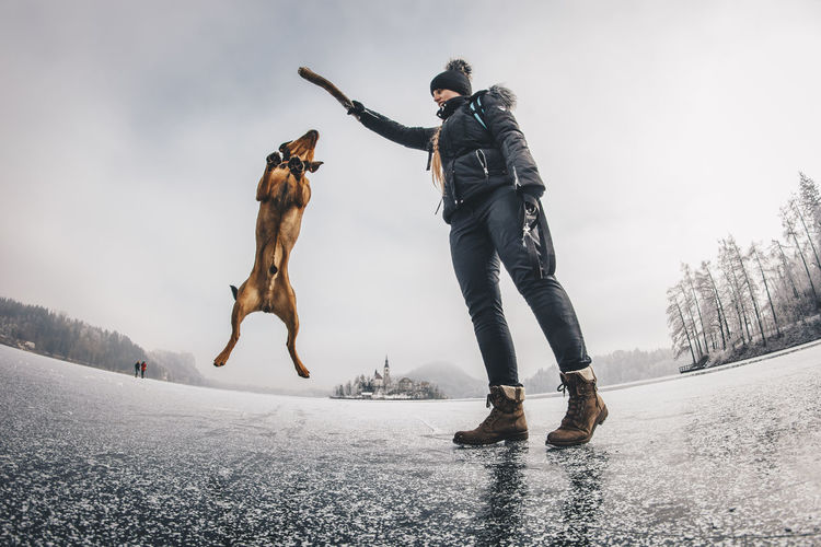 Low angle view of woman playing with dog on frozen lake
