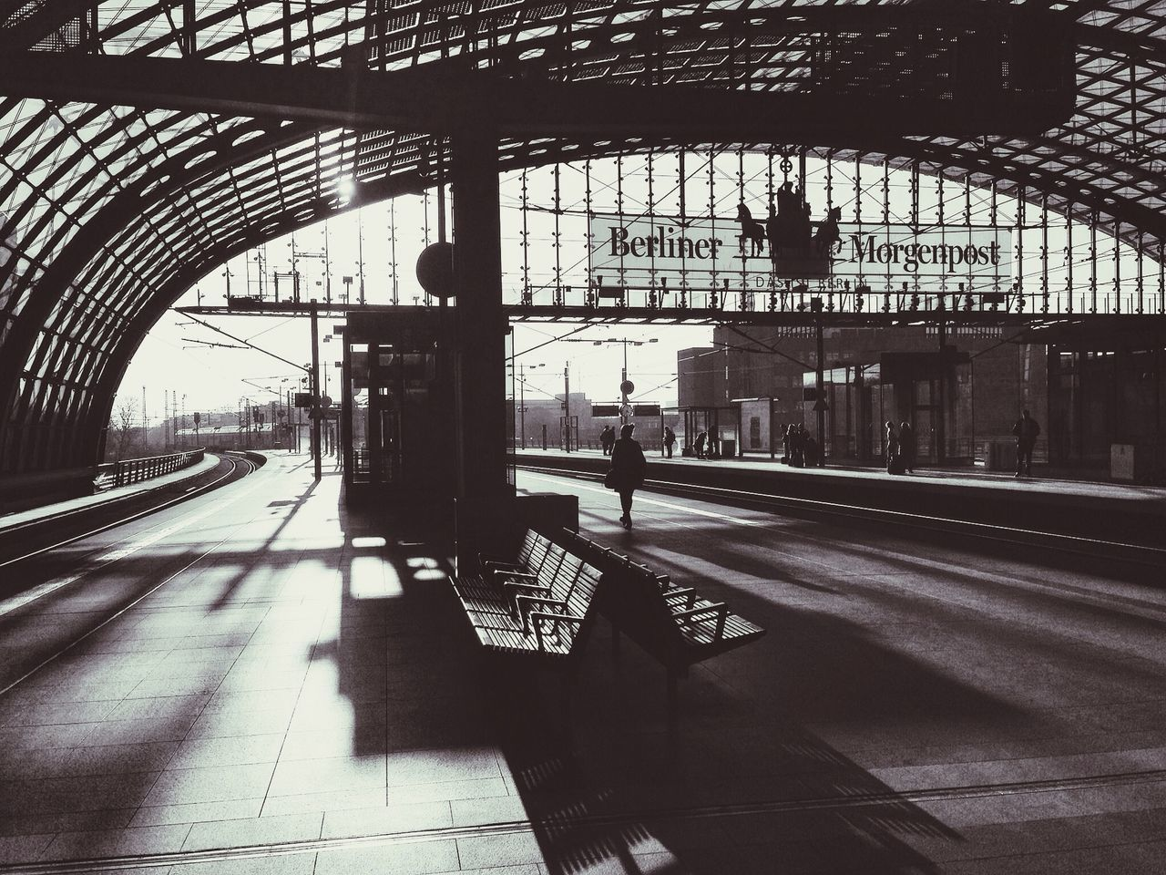 railroad station, transportation, railroad station platform, public transportation, architecture, rail transportation, built structure, indoors, travel, day, shadow, sunlight, real people, full length, city, one person, people