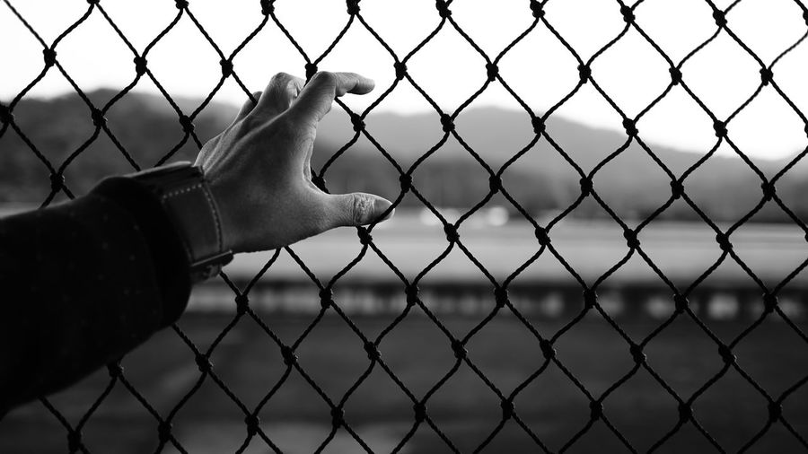 Close-Up Of Hand By Chainlink Fence Against Sky