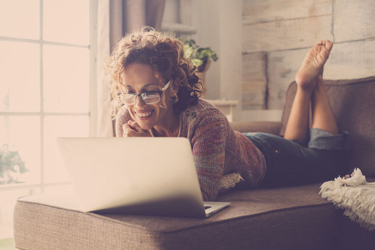 Woman smile and use an internet laptop connected to watch a movie or work easy at home in alternative office and lifestyle concept - freelance and free people with technology Laptop Wireless Technology Computer Using Laptop Technology One Person Communication Connection Sitting Young Adult Adult Women Furniture Lifestyles Real People Young Women Casual Clothing Home Interior Indoors  Hair Hairstyle Beautiful Woman Smiling Caucasian barefoot Relaxing Chatting Internet One Woman Only People Freelancer Freedom Office Building Exterior Business Window