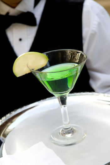Midsection Of Waiter Holding Martini Glass