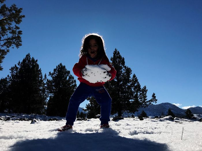 Full length of girl playing with snow against clear blue sky