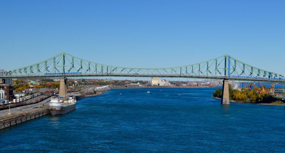 Suspension bridge over river against clear blue sky