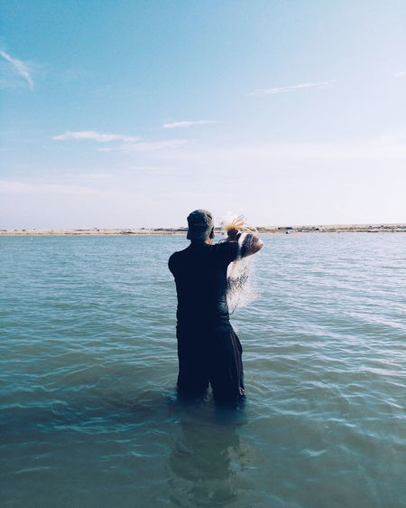 Rear view of young man standing in sea against sky