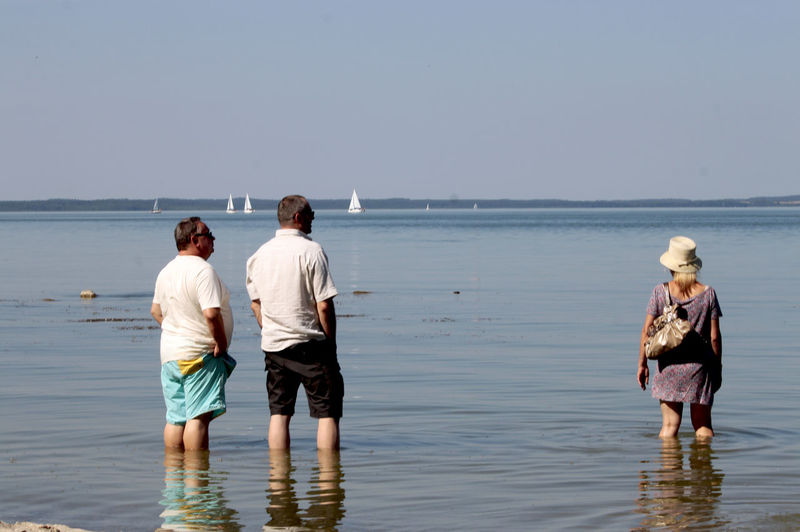 a trio standing in water Beauty In Nature Enjoying Life Fun Horizon Over Water Landscape Masuren Nature Outdoors Poland Sea Sky Standing Summer Tranquil Scene Tranquility Trio Vacations Water