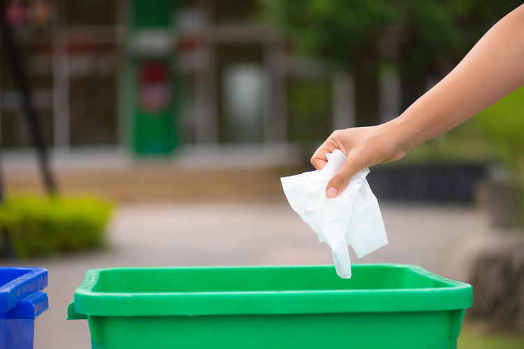 Cropped hand of person throwing paper in garbage bin