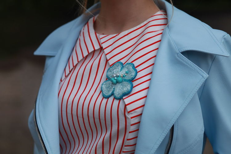 Midsection of woman with brooch