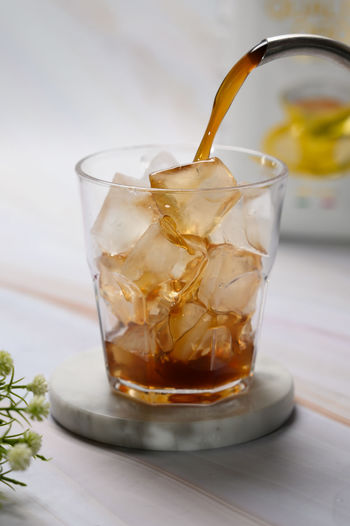 Close-up of tea being poured in glass full of ice cubes