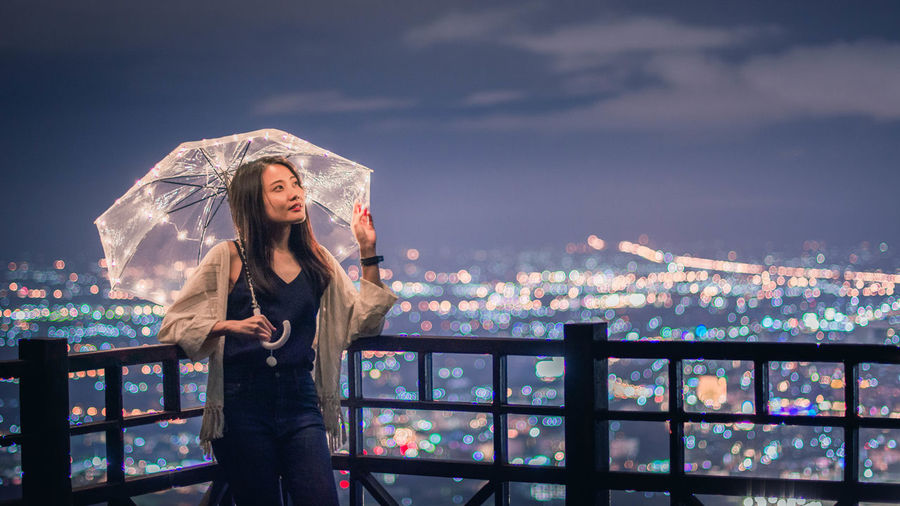 Woman with umbrella standing against illuminated cityscape at night