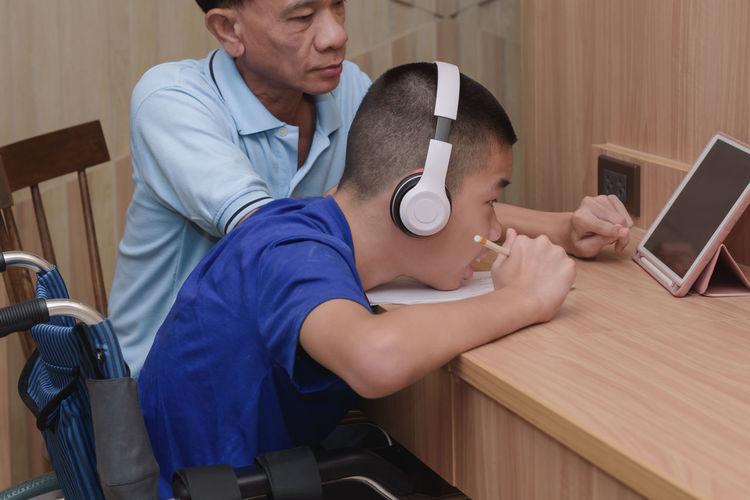 Boy wearing headphones looking at digital tablet at home