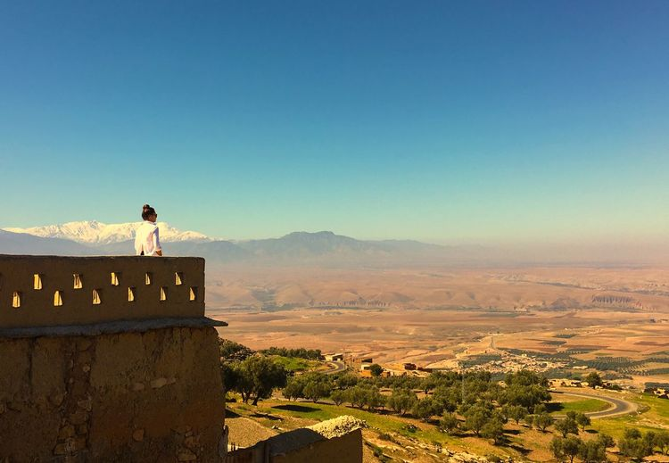 Woman looking at view against clear blue sky