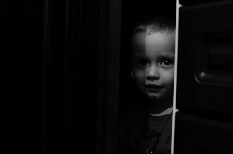 Portrait of cute boy seen through ajar at home
