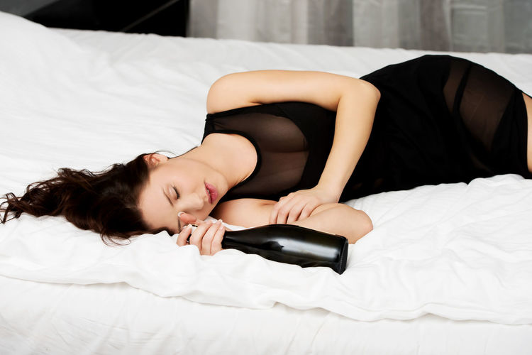 Drunk woman with wine bottle sleeping on bed at home