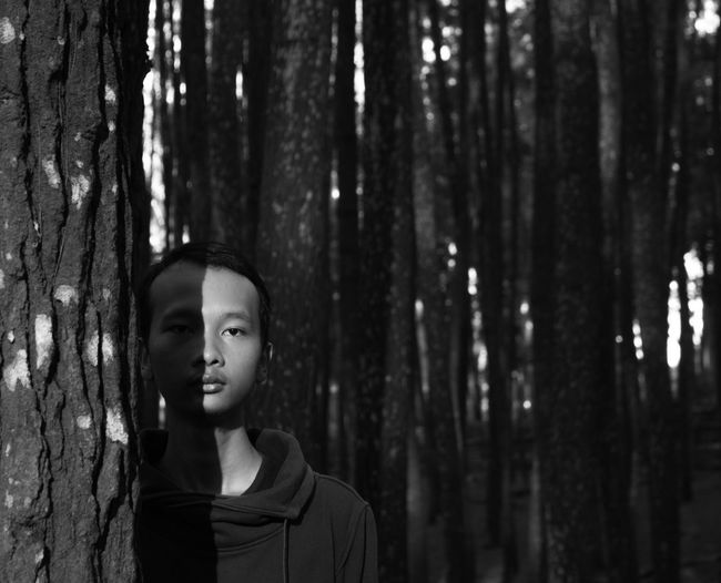Portrait of young man standing by tree trunk in forest
