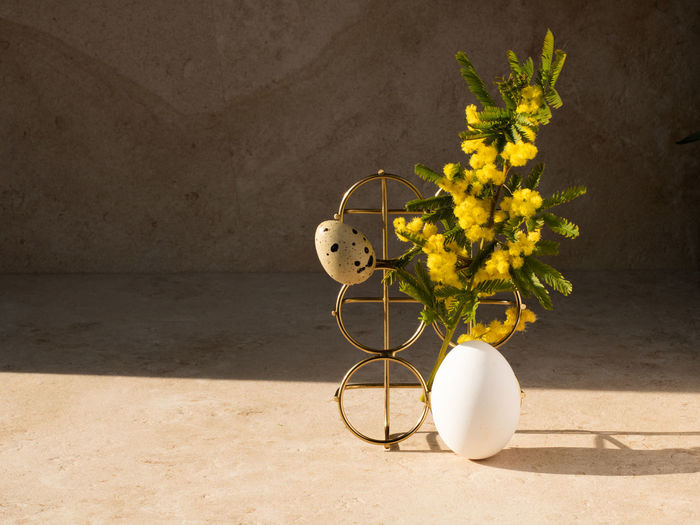 Flower vase on table against wall