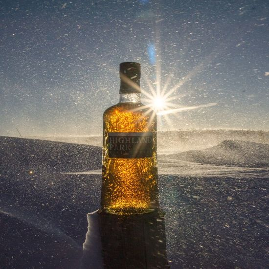 Digital composite image of glass and bottle on table against sky