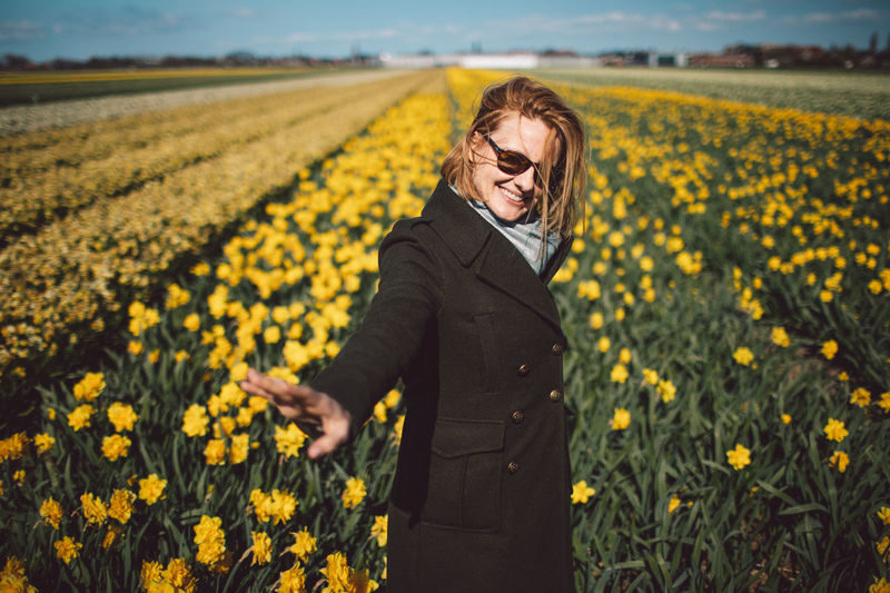 Woman standing on yellow narcissus flower field
